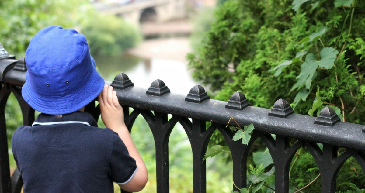 Feature - boy staring out to river beyond railings