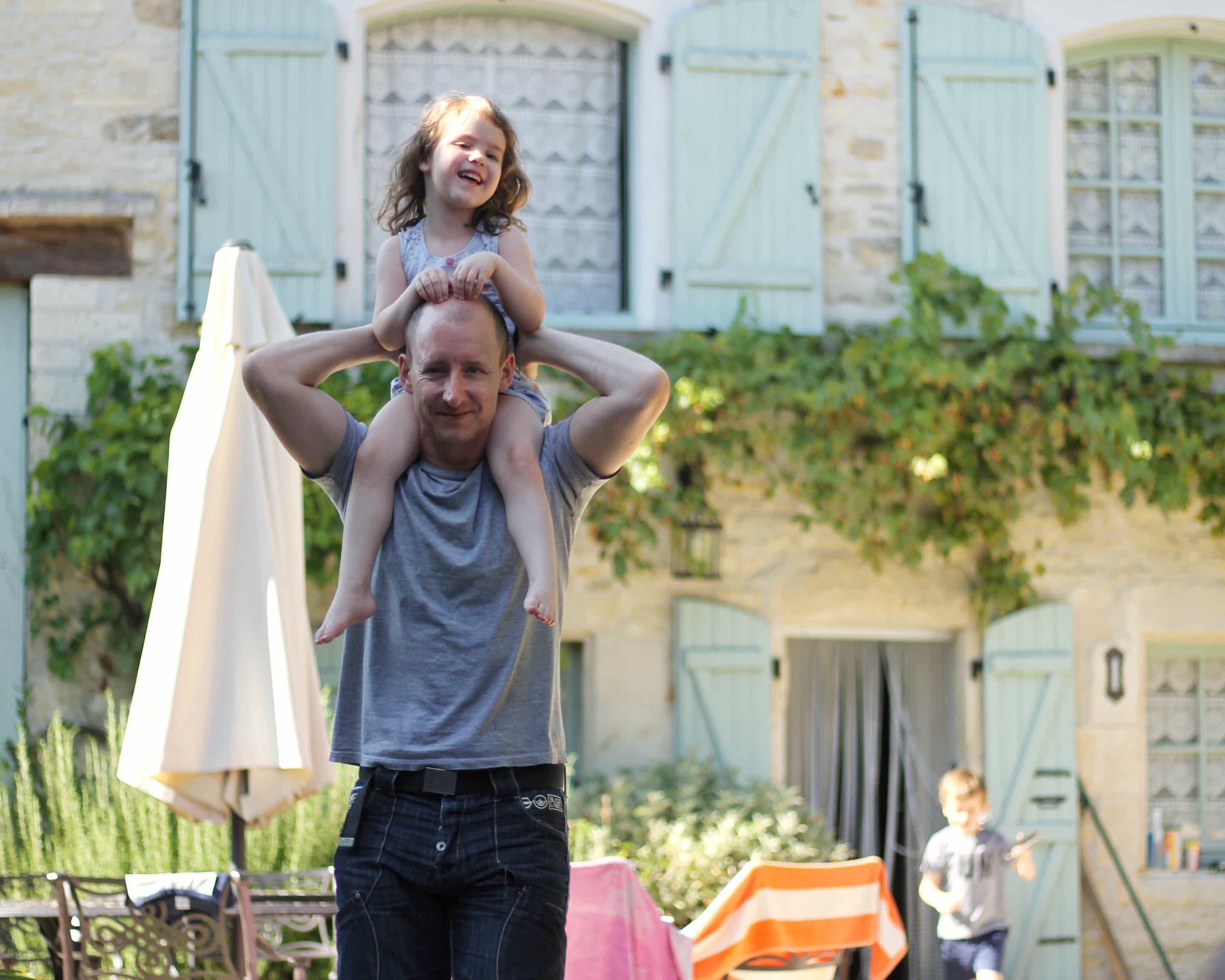 Matt in front of my parents' house with Littlest on his shoulders and Biggest in the background - french gites at Maison de Figuier