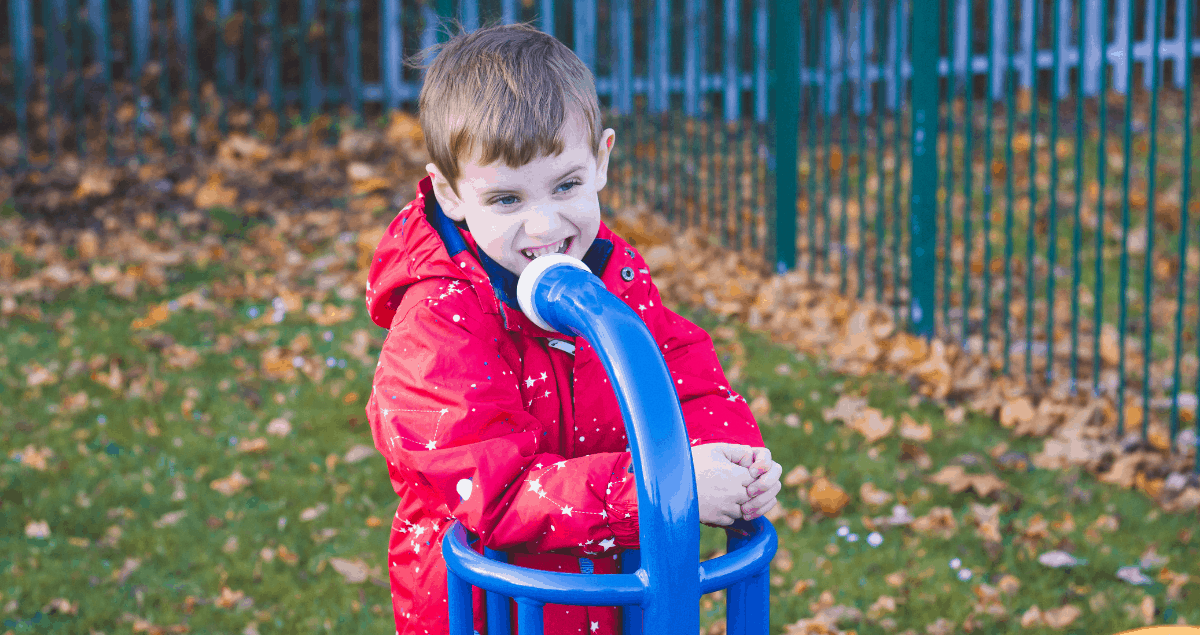 A boy in a red coat at a park