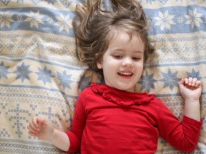 When the School Letter comes feature - small girl in red top lying on top of snowflake duvet