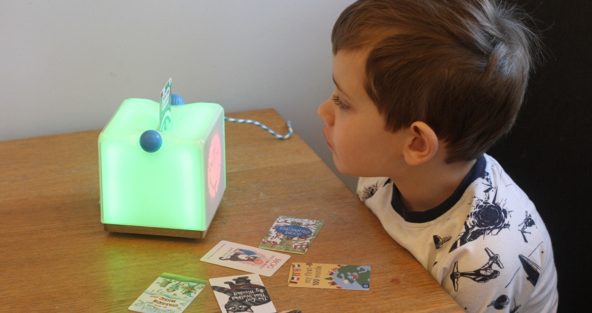 A boy using the light-up Yoto Clever Speaker