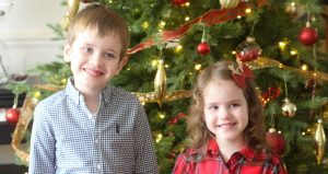 A small girl and boy holding in front of a christmas tree