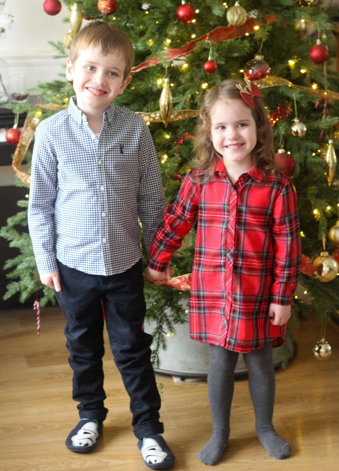 Boy and girl holding hands in front of a christmas tree