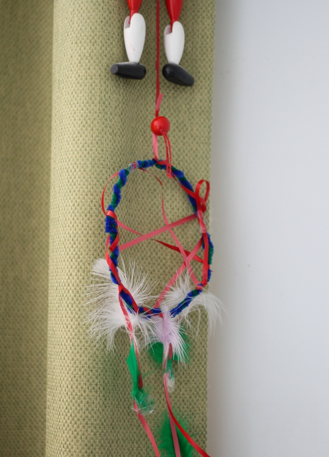A dream catcher made by a child, hanging down from a curtain with the legs of a wooden toy above