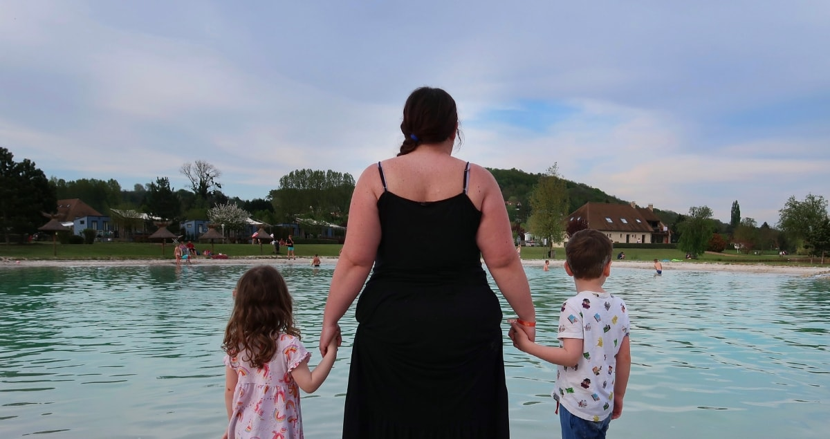 Woman hand in hand with boy and girl, looking out over a lake