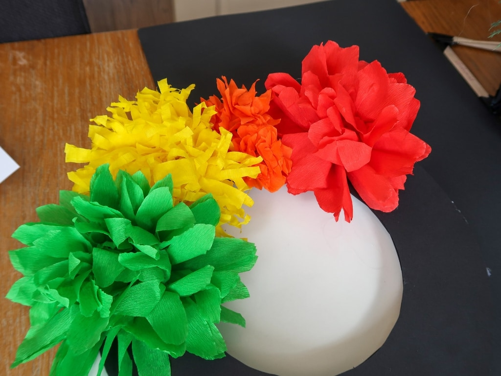 Some paper flowers partially filling the circle-shaped wreath
