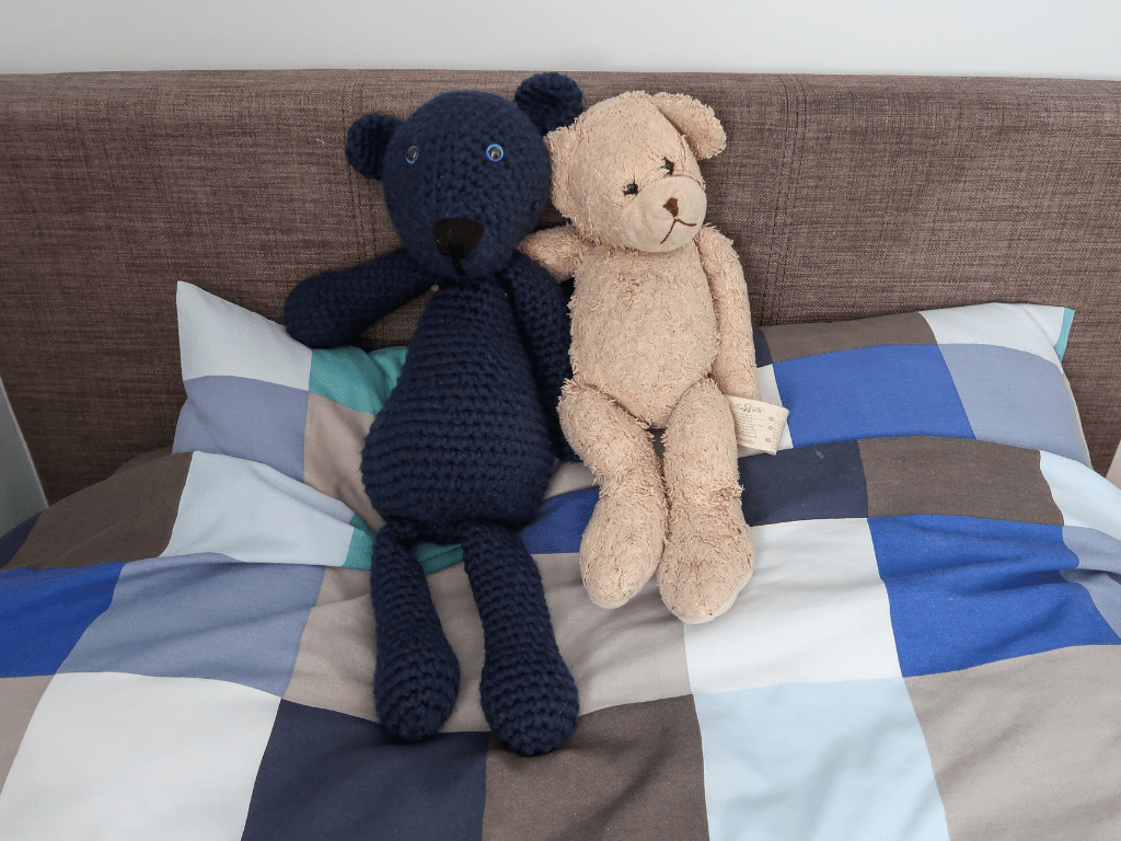 Two teddy bears, one brown, one blue, lying on a bed with a blue-checked duvet.