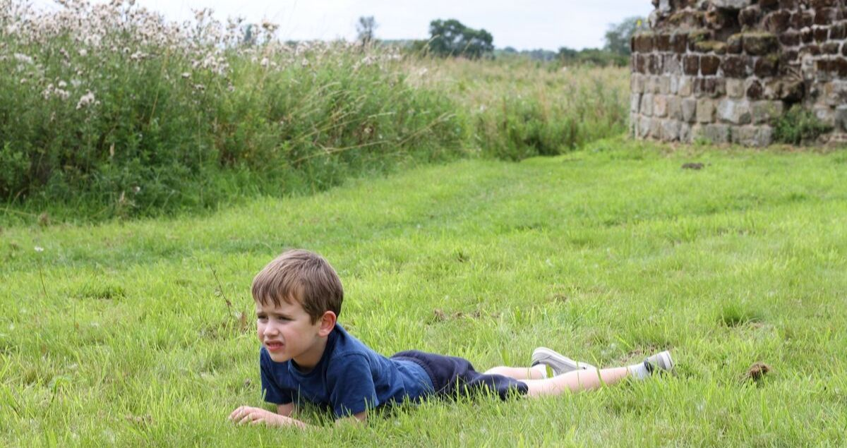 Boy lying on grass in front of castle ruins