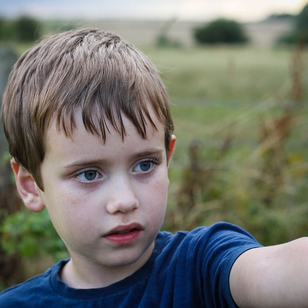 A boy with a field in summer behind him for autism or spoiled