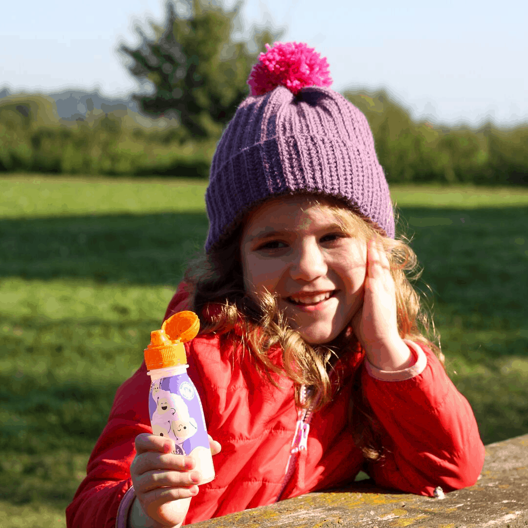 Small girl outdoors wearing a purple crochet hat