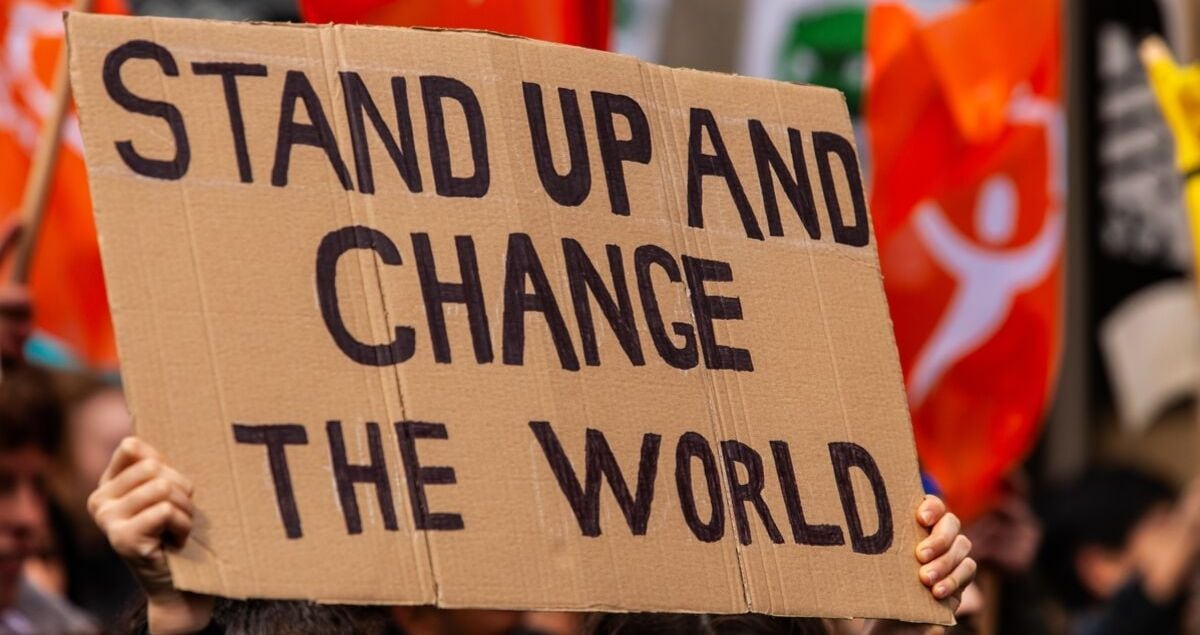 Homemade sign at environmental rally. A cardboard sign is seen close up, saying stand up and change the world, as eco-activists march for the environment on a street in Montreal, Canada
