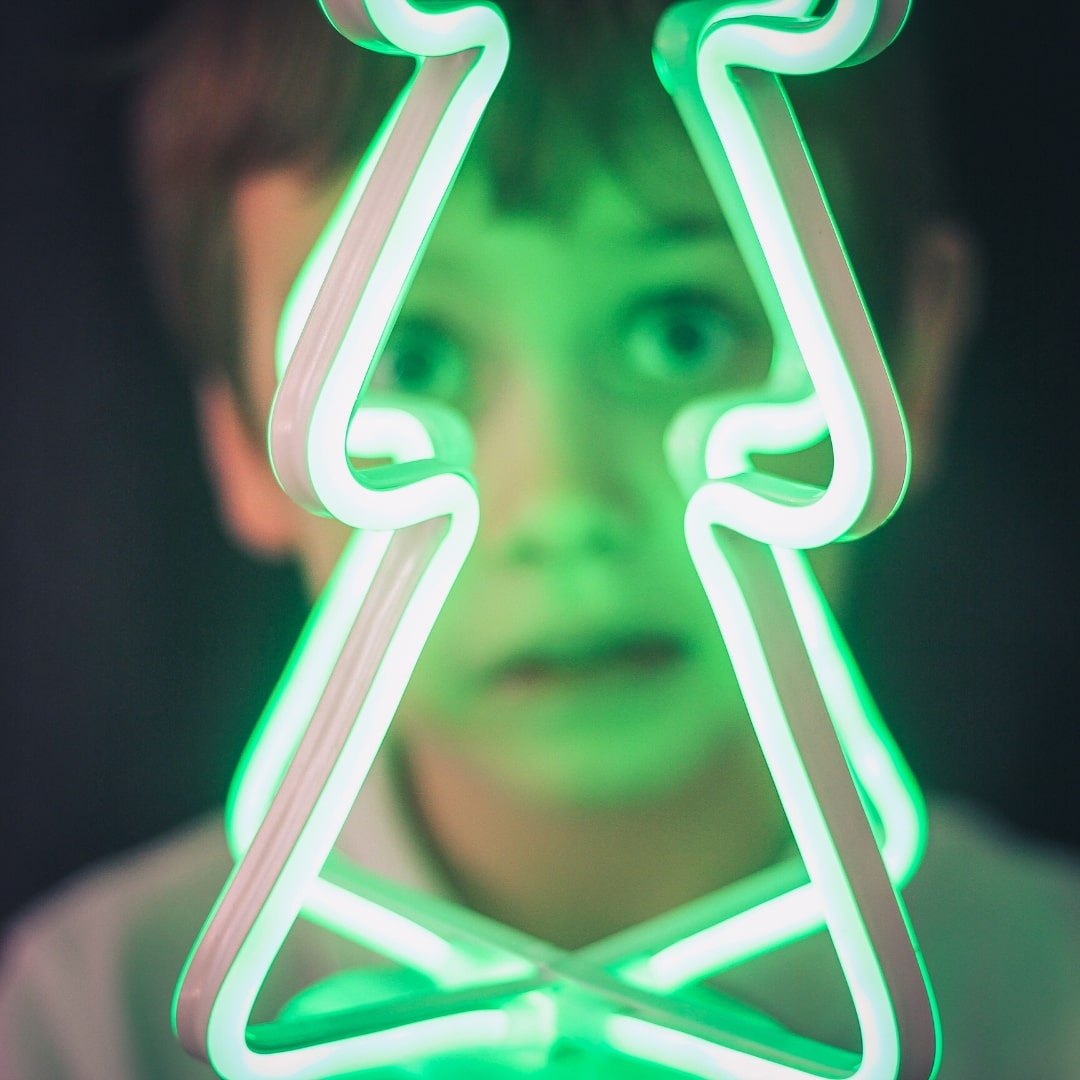 Face of a boy behind a green flourescent christmas tree lamp
