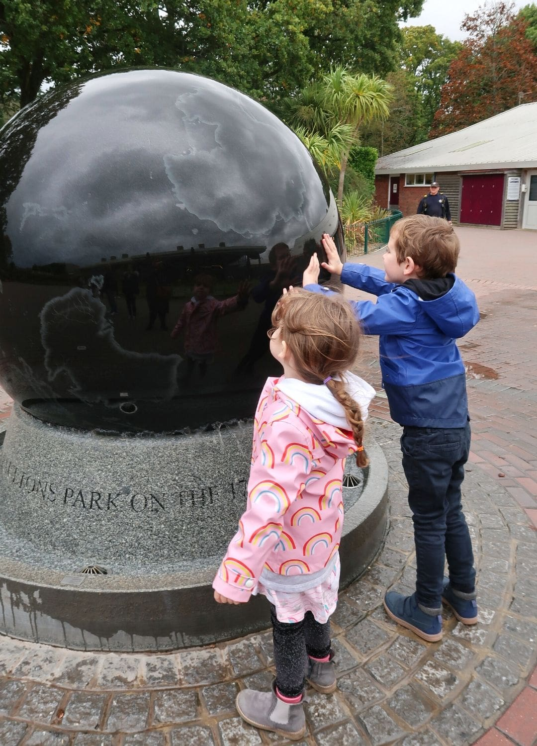 Globe Fountain near the entrance to Paulton's Park with small boy and girl touching it.