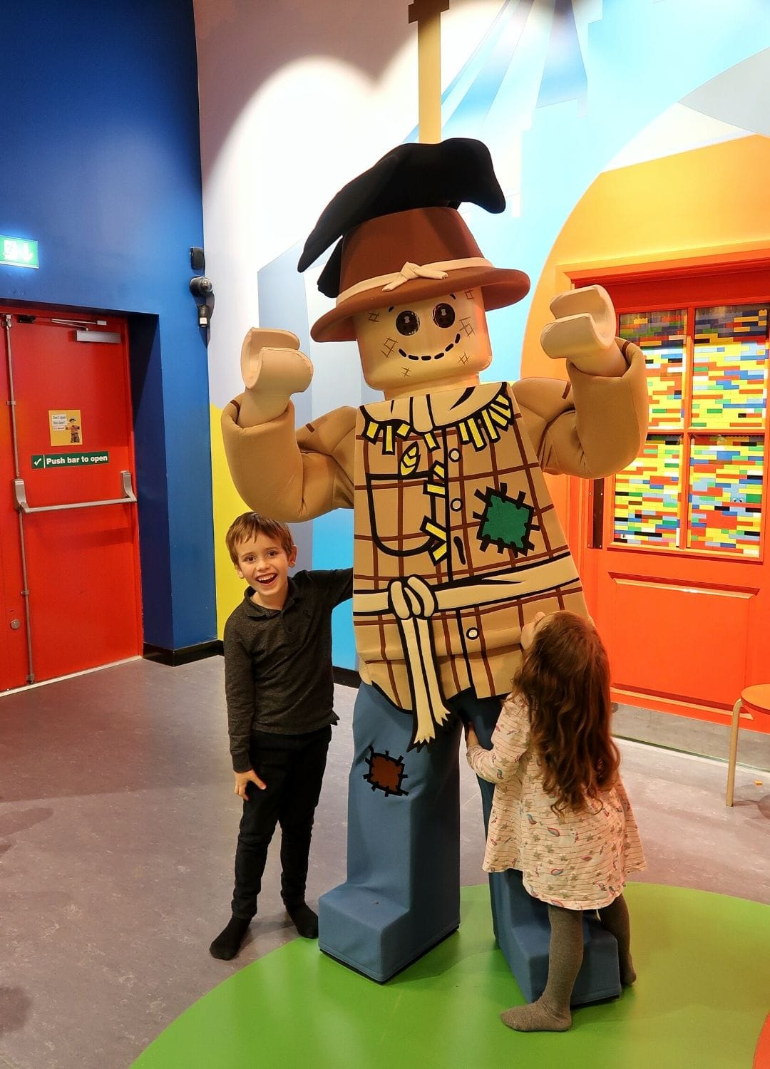 Boy and girl smiling in front of a person dressed as a lego character