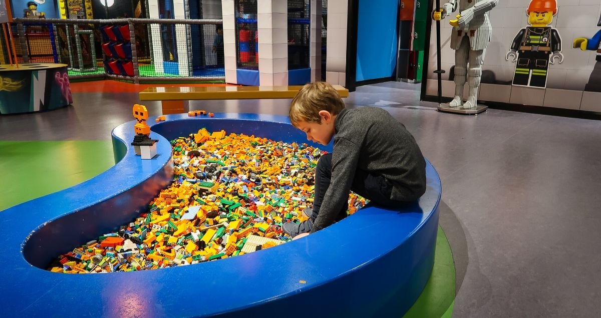Boy beding over a large pit full of coloured lego
