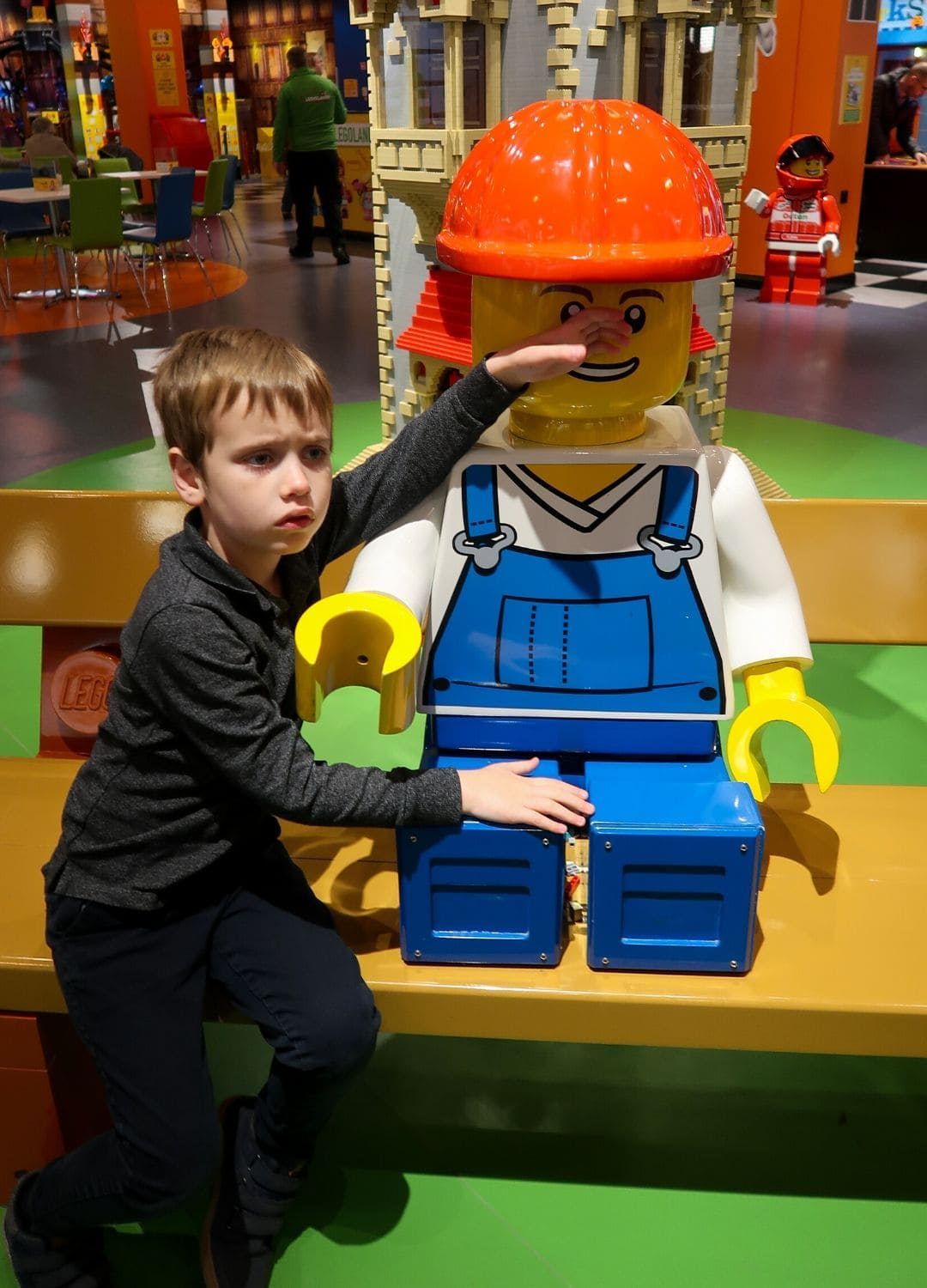Boy looking sad next to giant lego figure.