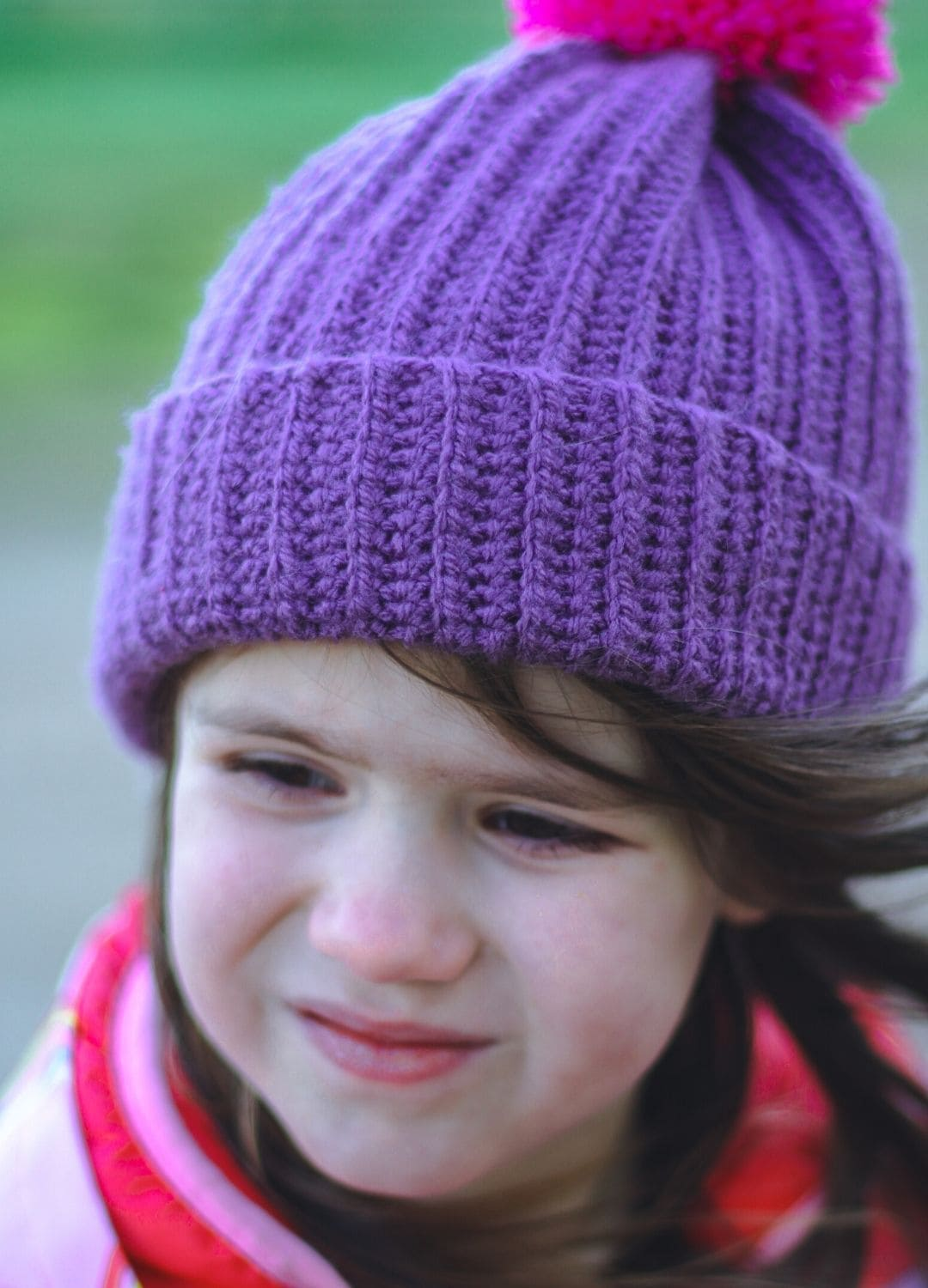 Close-up of small girl in purple bobble-hat