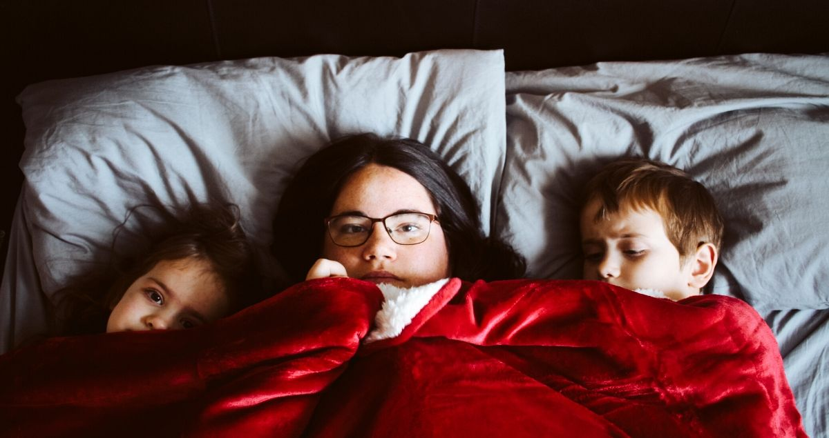 Mother and children in bed covered in red blanket